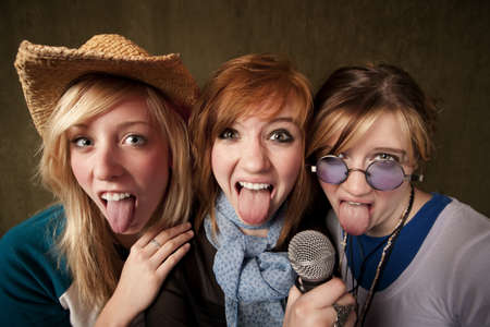 Portrait of three pretty young girls and tongues out with a microphone on green background photo