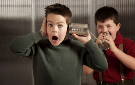 tin: Little boy getting shocking message from friend on tin can phone