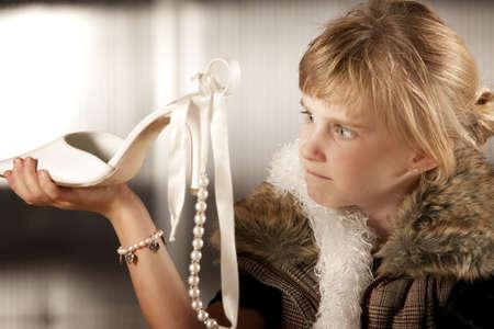 disdain: Linda ni�a en el vestuario buscando un zapato puntiagudos Foto de archivo