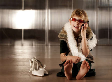 Cute young girl in dress-up clothes and red sunglasses talking on cell phone
