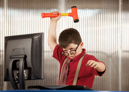 dweeb: Nerdy young boy smashing his computer with a hammer