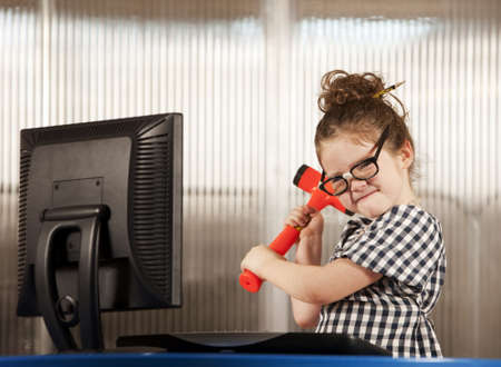 dweeb: Nerdy young girl smashing her computer with a hammer Stock Photo