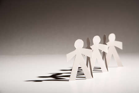 Line Of Cutout Paper Dolls Throwing A Shadow Stock Photo Picture And Royalty Free Image 4569771