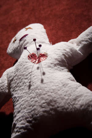 White Voodoo Doll with Pins in its Heart on Red Background