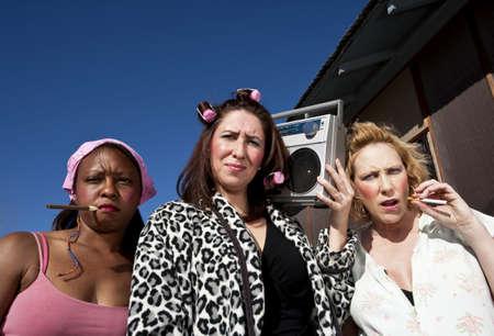 Portrait of three trashy women outdoors