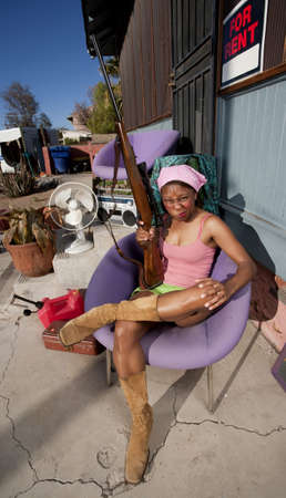 guard house: Black woman with rifle in front of house with messy yard