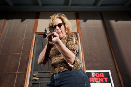 firepower: Blonde woman on her front porch with a rifle