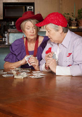 rummy: Ladies wearing red hats playing a hand of cards