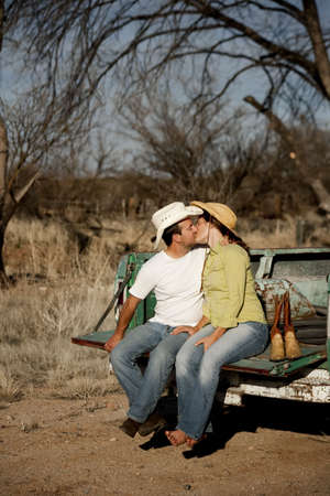 Man and woman in cowboy hats kissing on back of pickup truck Stock Photo