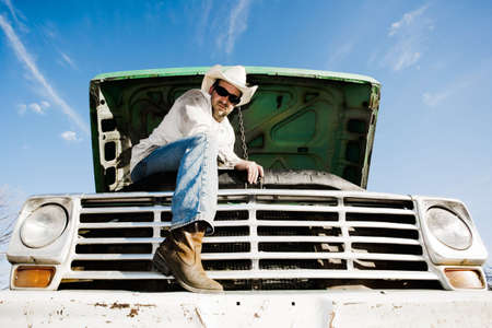 Man in cowboy hat under the hood of truck photo