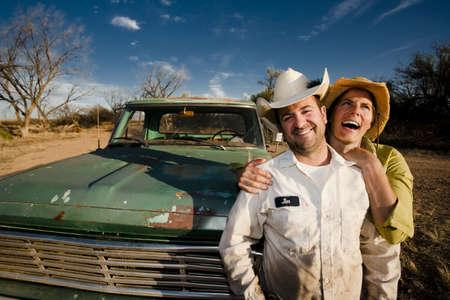 camioneta pick up: El hombre y la mujer en los sombreros de cowboy con viejos camiones