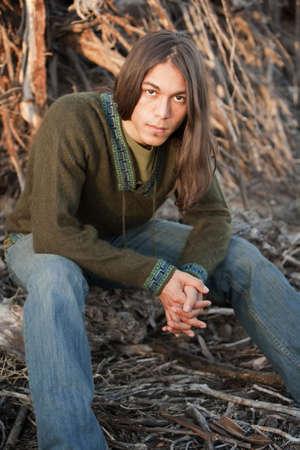 mann mit langen haaren: Gut aussehender junger Mann mit langen Haaren in einem Outdoor-Einstellung