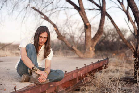 Handsome young man with long hair in an outdoor setting Stock Photo