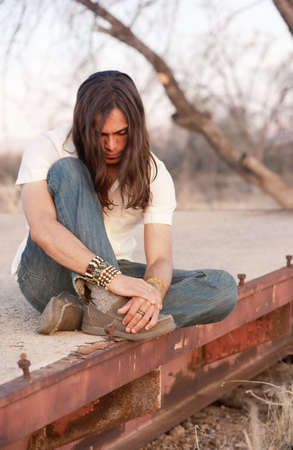 downcast: Handsome young man with long hair in an outdoor setting Stock Photo