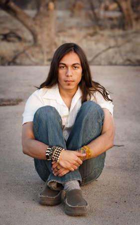 indio americano: Apuesto joven con el pelo largo en un establecimiento al aire libre