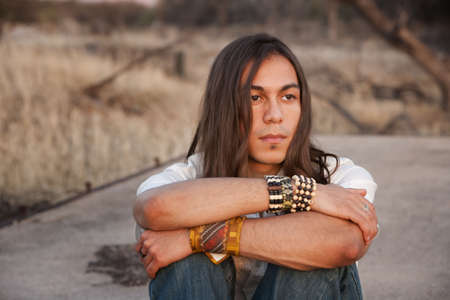 native indian: Handsome young man with long hair in an outdoor setting Stock Photo