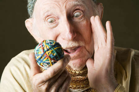 stretchy: Senior man in knit cap contemplating a colorful rubber band ball
