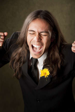 Handsome man screaming in formal jacket with boutonniere