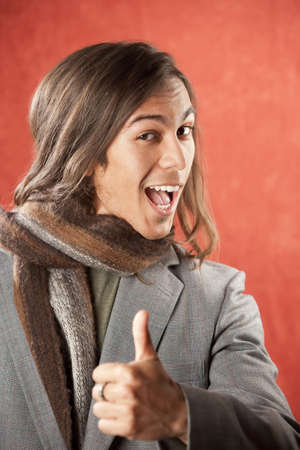 Closeup Portrait of a Handsome Young Man Making a Thumbs Up Gesture photo