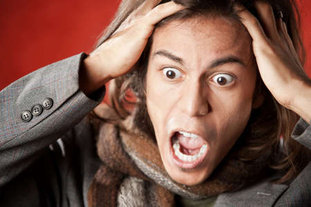 crazed: Closeup Portrait of a Handsome Young Man with Long Hair Screaming