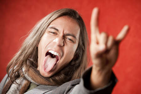 crazed: Closeup Portrait of Handsome Young Man with Long Hair Making Hand gesture and Sticking Out Tongue Stock Photo