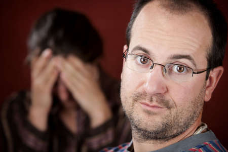 spat: Guilty man with upset woman in the background Stock Photo