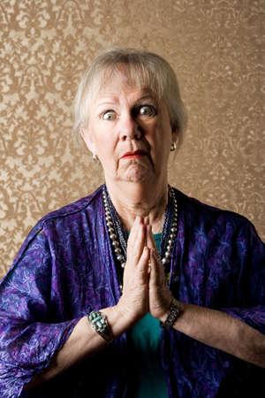 Funny senior new age lady in purple praying photo