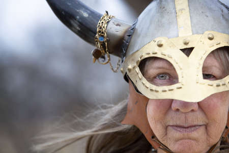 Closeup portrait of Viking woman in helmet with horns