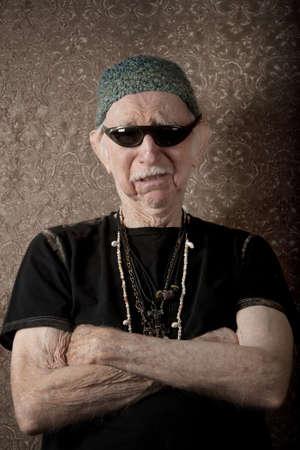 Senior stoere vent in breien cap leunend tegen een muur