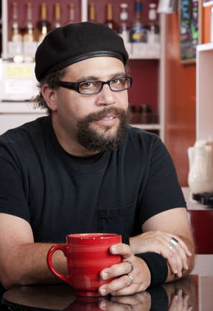 Man with facial hair and beret in coffee house photo