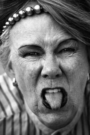 Closeup of rude old woman sticking out her tongue photo