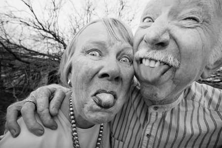 Closeup portrait of crazy elderly couple outdoors sticking out tongues photo