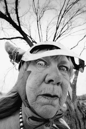 Crazy old woman wearing a Viking helmet Фото со стока