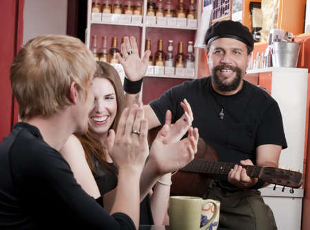 Couple in coffee house listening to a guitarist photo