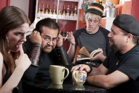 Three friends listening to bad male poet with smoky cigarette in a coffee house Stock Photo - 4781098