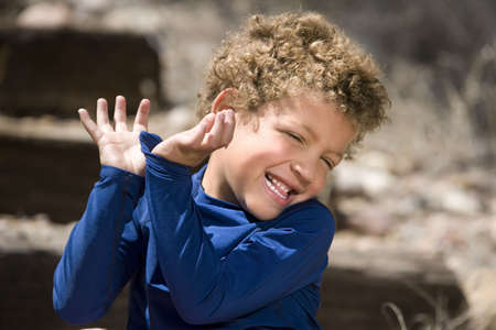 giggle: Portrait of cute boy with curly hair laughing outdoors