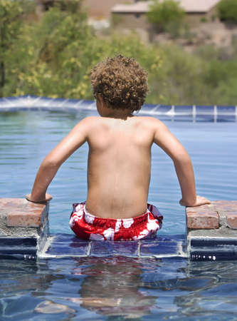 Young boy sitting on the edge of a swimming pool