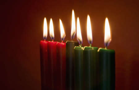 Seven Kwanzaa candles with flames lit on neutral background