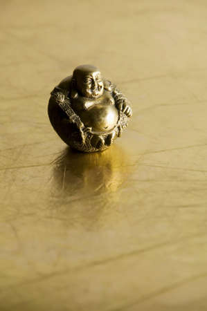 Buddha statue with big belly on shiny gold background