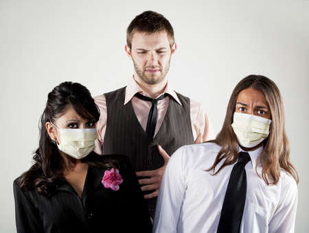 epidemic: Tall man with stomach upset and coworkers wearing masks Stock Photo