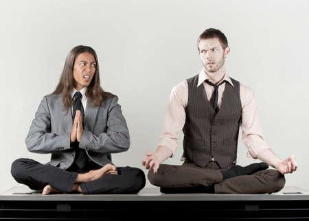 Two businessmen meditating on their office desk Banque d'images