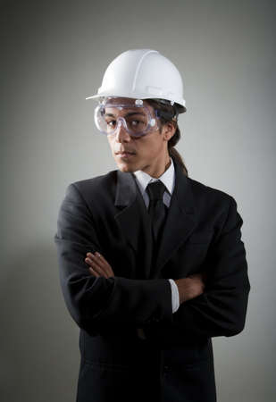 Handsome young mixed race man in hard hat and safety goggles