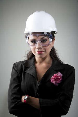 ハード帽子と安全ゴーグルでハンサムな若い女性
