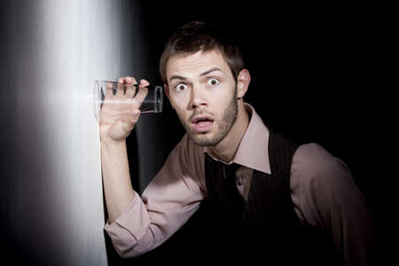furtive: Handsome young man using glass against wall to eavesdrop