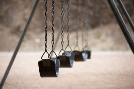 playground equipment: Old style playground swings with chains and rubber seats Stock Photo