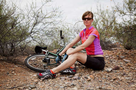 gear handle: Young woman sitting next to mountain bike