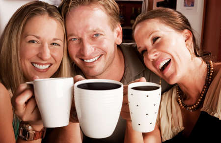 cup four: Three friends in a coffee house toasting with their cups Stock Photo