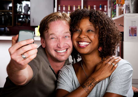 Caucasian man and African American woman taking picture in coffee house with cell phone photo