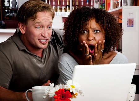 pornography: Caucasian man and African American woman in coffee house with laptop computer