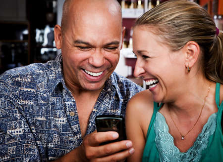 chuckle: Attractive couple in a coffee house with cell phone Stock Photo